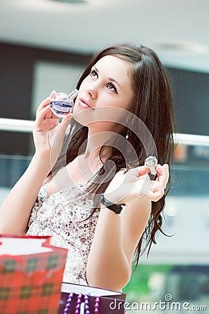 La muchacha prueba un olor apenas las bebidas espirituosas compradas
