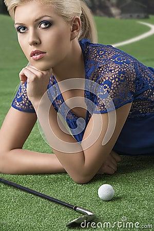 La muchacha rubia atractiva paga golf con la mano