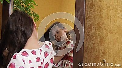 La muchacha se está peinando el pelo por el espejo La niña se está peinando el pelo El niño se está sentando por el espejo almacen de video
