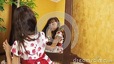 La muchacha se está peinando el pelo por el espejo La niña se está peinando el pelo El niño se está sentando por el espejo almacen de metraje de vídeo