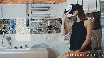 La muchacha se sienta en retrete en cuarto de baño en vidrios de la realidad virtual juego Mirada alrededor almacen de metraje de vídeo