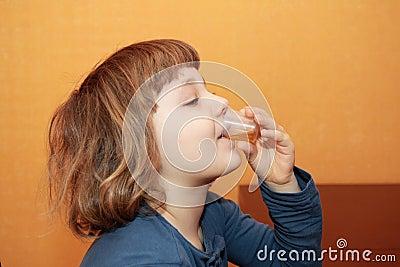 La muchacha toma la medicina. Él bebe el jarabe