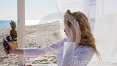 La muchacha toma las fotos en el teléfono móvil, playa en el verano, selfie en la memoria, vacaciones en las islas tropicales, mu almacen de metraje de vídeo