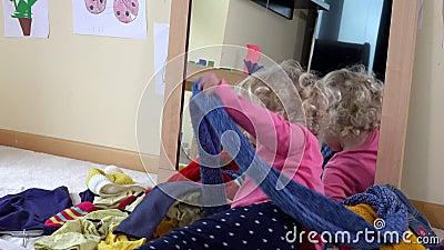 La muchacha traviesa que miente entre la ropa cerca duplica El niño travieso se divierte en casa almacen de metraje de vídeo