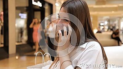 La muchacha utiliza el teléfono en la alameda que se sienta en un banco metrajes