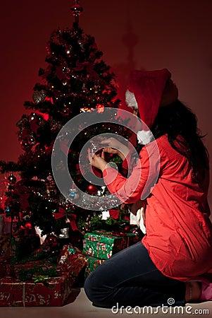 La mujer adorna el árbol de navidad en noche