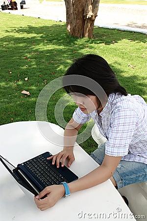 La mujer asiática atractiva está al aire libre con la computadora portátil
