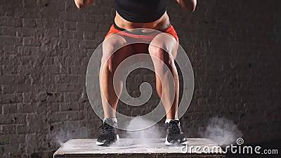 La mujer atlética apta encajona saltos en el gimnasio abandonado de la fábrica El ejercicio intenso es parte de su aptitud cruzad metrajes