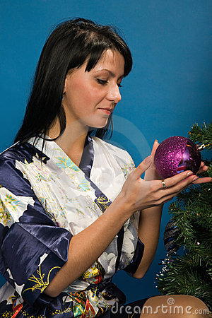 La mujer bonita adorna un árbol de navidad