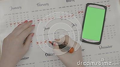 La mujer da fechas del período de la marca en control de la natalidad del planeamiento del calendario mientras que mira smartphon almacen de metraje de vídeo