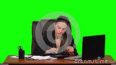 La mujer de negocios en el lugar de trabajo se dedica a las finanzas, hace cálculos en una calculadora y llena los papeles Verde almacen de metraje de vídeo