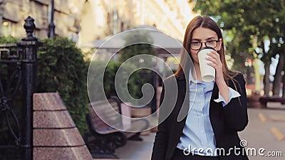 La mujer de negocios joven está caminando en la calle y bebe el café y smartphone con en la hora de la almuerzo almacen de metraje de vídeo