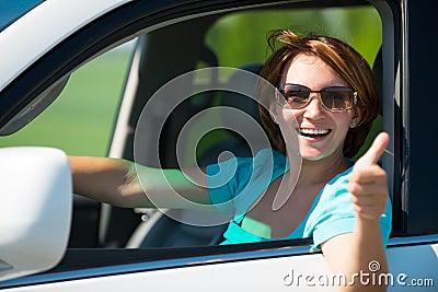 La mujer en el nuevo coche blanco en la naturaleza con los pulgares sube la muestra