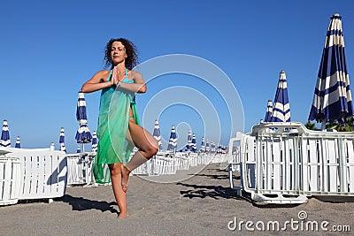 La mujer en traje de baño y pareo se coloca en la playa