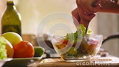La mujer hermosa joven en la ropa casera está cocinando en la cocina Ella hace un poco de ensalada fresca con lechuga verde almacen de video