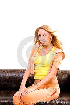 La mujer hermosa joven se sienta en el sofá