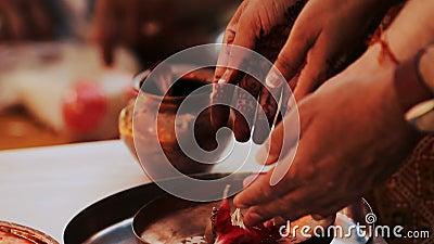 La mujer hindú pone los pétalos rojos en la placa de bronce