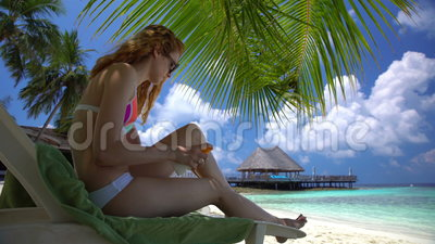 La mujer joven con las piernas hermosas utiliza la protección solar en la playa tropical metrajes