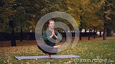 La mujer joven flexible está equilibrando en un pie que lleva a cabo las manos en namaste que disfruta de práctica individual en  almacen de metraje de vídeo