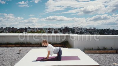 La mujer joven flexible está haciendo ejercicio complejo de la yoga que estira en la cámara lenta almacen de metraje de vídeo