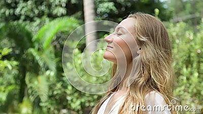 La mujer joven hermosa con el pelo rubio largo toma una respiración profunda almacen de video