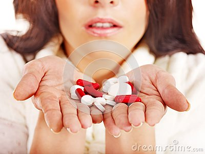 La mujer joven que tiene gripe toma píldoras.