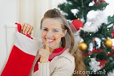 La mujer joven sonriente puso el regalo en calcetines de la Navidad
