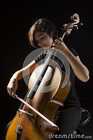 La mujer joven toca el violoncelo