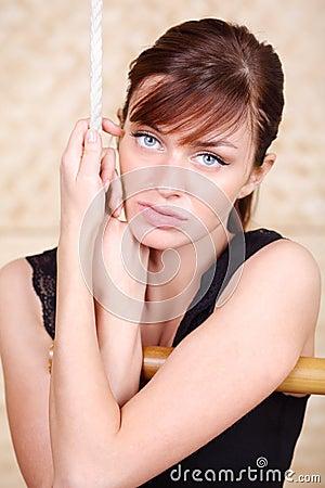 La mujer melancólica hermosa se sostiene en la escalera de cuerda de bambú.