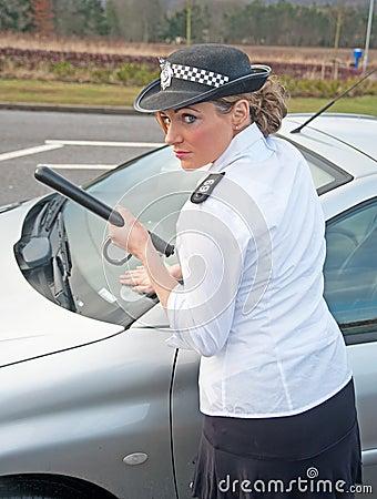 La mujer policía trata del coche gravemente estacionado