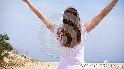 La mujer salta con alegría a lo largo de la trayectoria de la arena Hembra despreocupada que aumenta los brazos para arriba y que metrajes