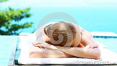 La mujer sonriente en balneario acuesta al lado de piscina