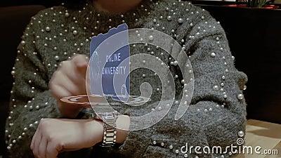 La mujer utiliza el reloj del holograma con la universidad en línea del texto metrajes