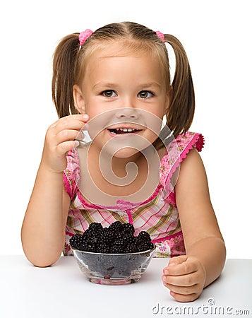 La niña alegre está comiendo la zarzamora