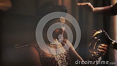 La novia majestuosa mira en el espejo mientras que la mujer ajusta casarse los accesorios en su cabeza almacen de metraje de vídeo