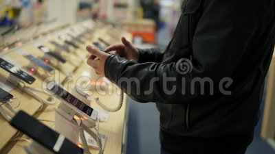 La opinión del primer de un ` s del hombre joven da elegir un nuevo teléfono móvil en una tienda Él está intentando cómo trabaja almacen de video