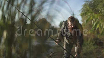 La pêche barbue d'homme avec une canne à pêche, laisse sa tige sur la berge et marche loin Fisher est engagé dans un passe-temps clips vidéos