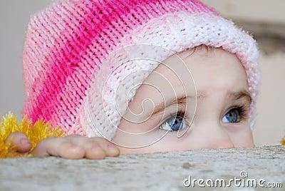 La pequeña muchacha mira hacia fuera detrás de un parapeto