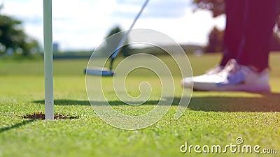 La persona juega al golf, pone una pelota en un agujero almacen de metraje de vídeo