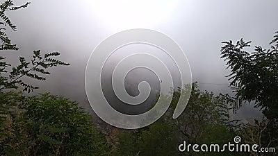 La persona scende sulla cerniera sopra la scogliera, le nuvole si muovono su per la montagna stock footage