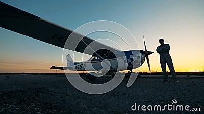 La persona se levanta en una pista cerca de un pequeño avión, cierre almacen de metraje de vídeo