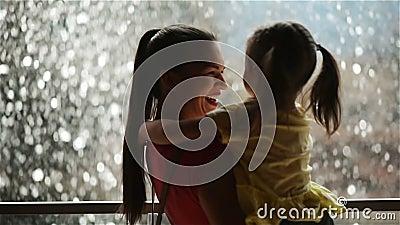 La petite fille douce est étreignante et embrassante sa belle jeune maman Jour de mères heureux La cascade est sur le fond banque de vidéos