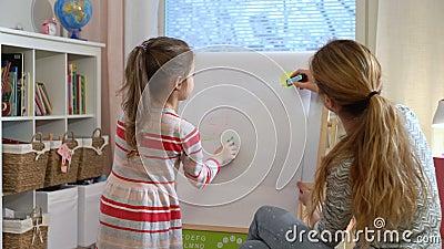 La petite fille et sa mère dessinent avec les crayons colorés banque de vidéos