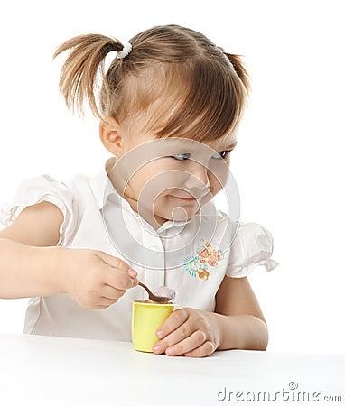 La petite fille mange du yaourt