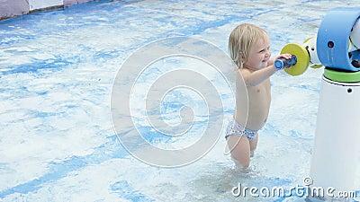 La petite fille mignonne joue avec le canon à eau dans la piscine banque de vidéos