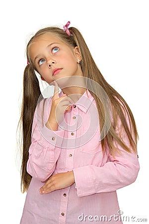 La petite fille mignonne pense le regard vers le haut sur le blanc