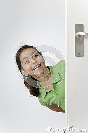 La petite fille se cache derrière la trappe pour l amusement