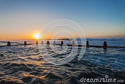 La piscina de marea del océano agita salida del sol