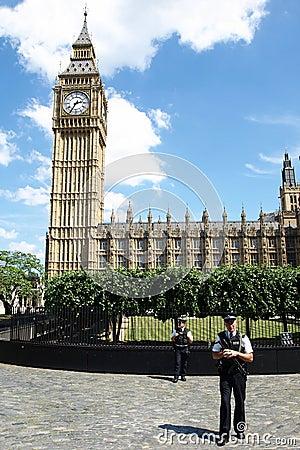 La policía coloca al protector fuera del palacio de Westminster Imagen de archivo editorial