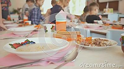 La preparazione per un pranzo irrompe l'asilo I bambini si siedono alla tavola con cibo cotto Il Russo stock footage